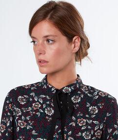 Chemise fleurie nouée au col noir.